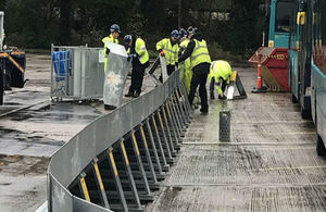 Picture shows workers in yellow jackets assembling metal barriers in a concreted area with buses parked to the right