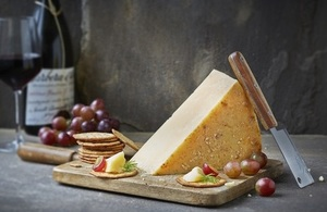 Image of a cheeseboard with a glass of wine in the background