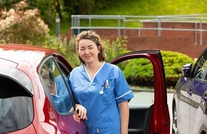 Nurse standing outside her car in a hospital car park