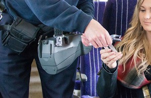 Image of rail ticket inspector punching a ticket for a young rail commuter.