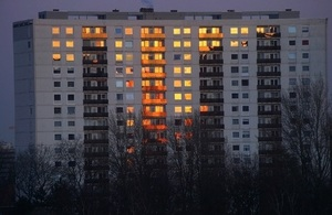 Big apartment block on a winter's evening with bare trees in foreground