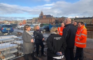 Minister Pow and Emma Howard Boyd stood facing a group of five Environment Agency staff members and local officials next to the Great Yarmouth flood barrier