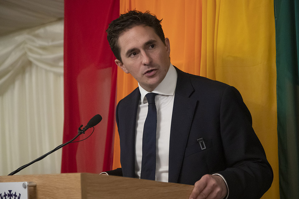 Minister for Defence People and Veterans Johnny Mercer speaking at the LGB20 reception with a rainbow flag behind him