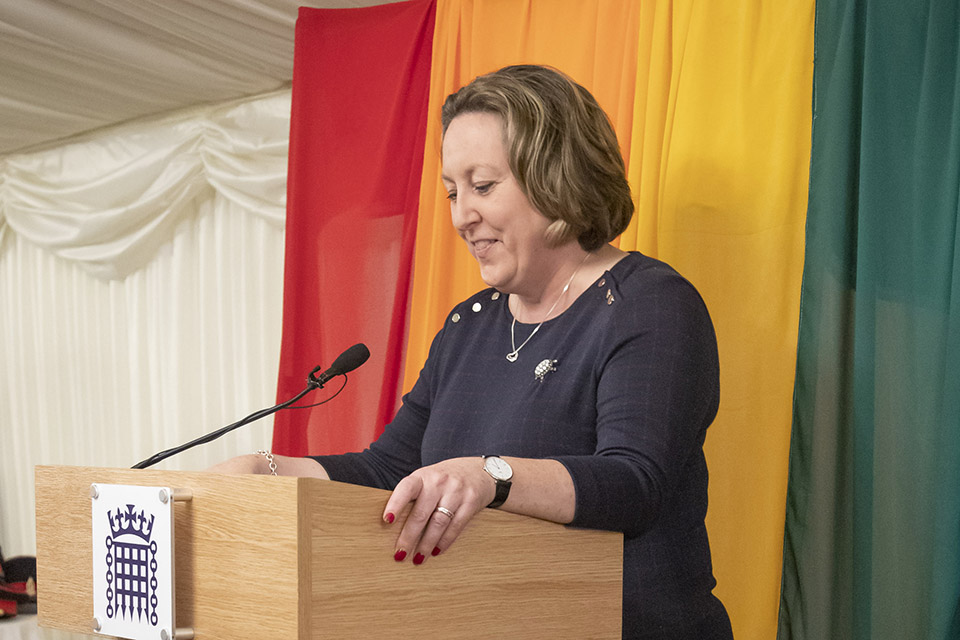 Minister of State for the Armed Forces Anne-Marie Trevelyan speaking at the LGB20 reception with a rainbow flag behind her
