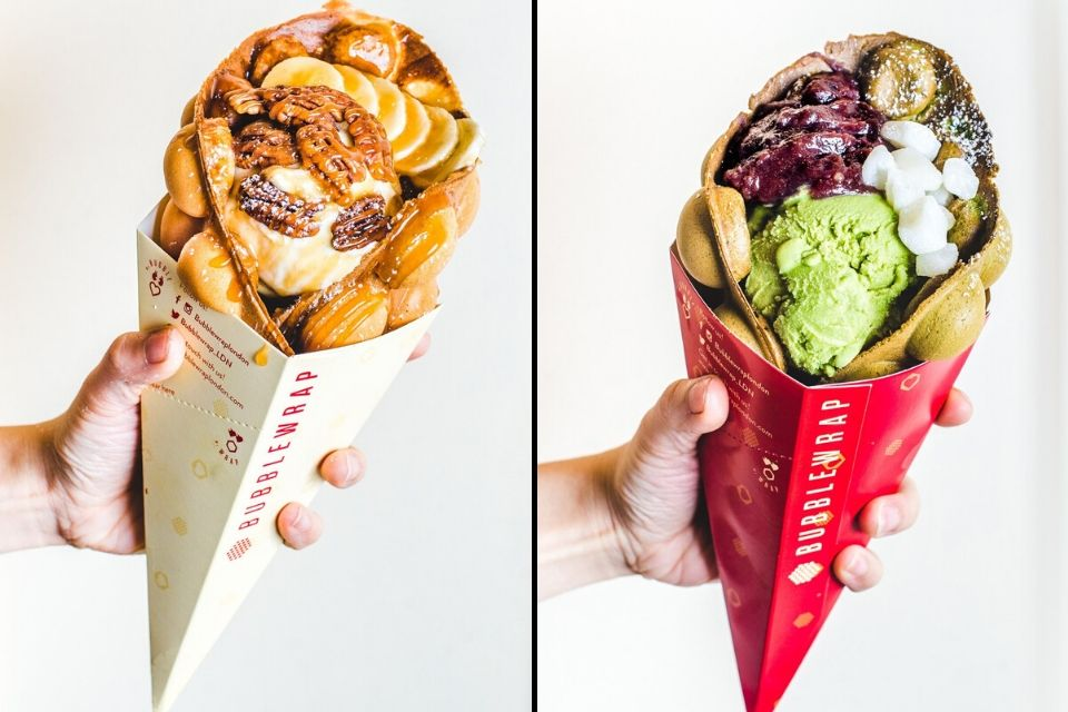 two hands holding waffles with ice cream inside