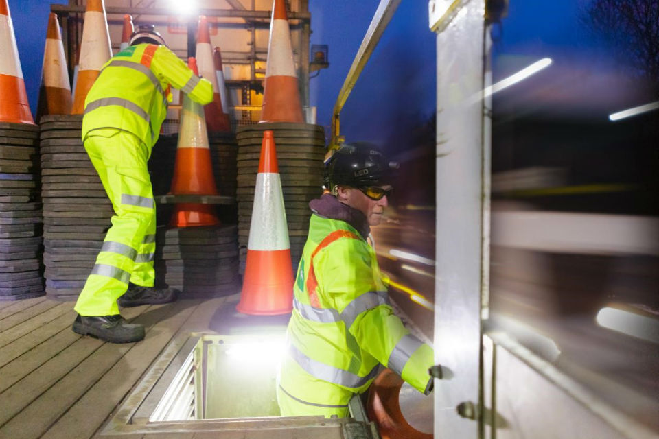 Highways England workers laying cones manually