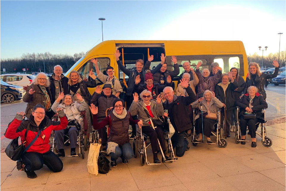 Photo of a group of people standing outside a yellow minibus purchased by the Denby Dale Centre as part of their volunteer car service.