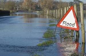 A flood warning sign on a closed country road next to water logged fields.