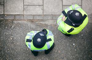 2 police officers standing in the street, photographed from above