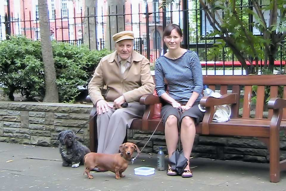 2 people seated on a garden bench with dogs at their feet