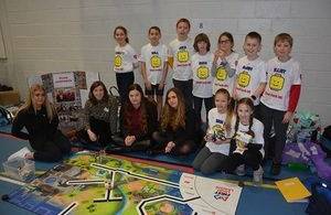Group of young schoolchildren and adults prepare for their regional final in the Lego League