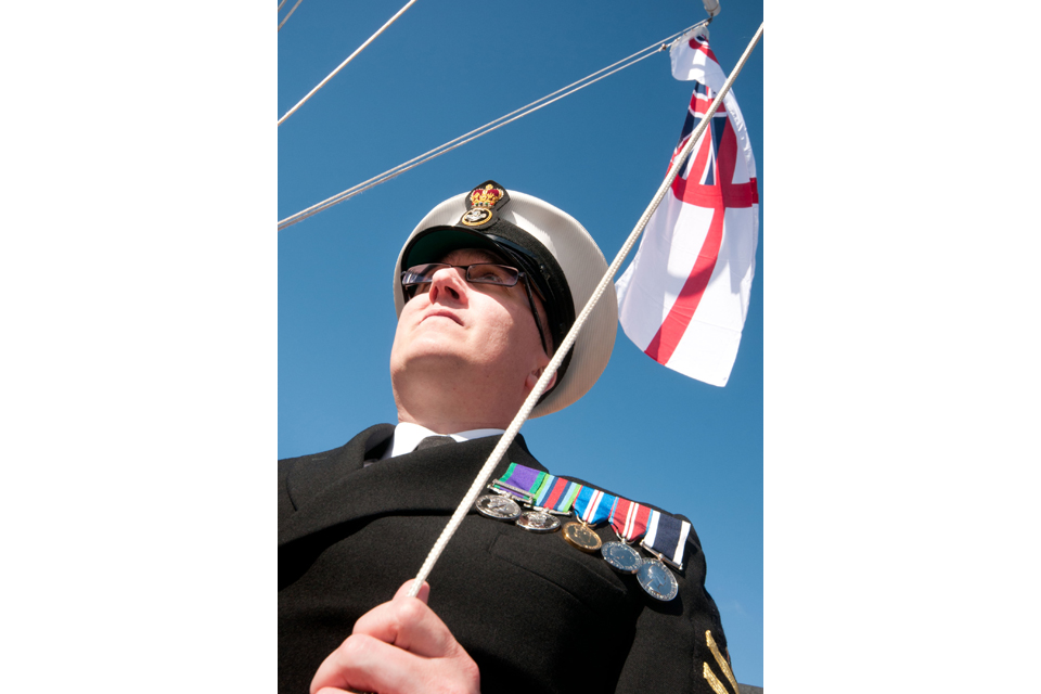 A Royal Navy reservist hoists the White Ensign at HMS Dalriada