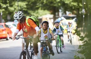 A group of children riding bicycles led by a Bikeability instructor