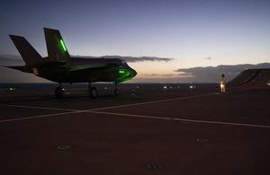 Image depicts F-35 Lightning jet on HMS Queen Elizabeth flight deck at sunset