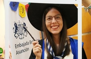 A woman wearing a robe, wizard hat, round glasses and holding a wand smiles at the camera