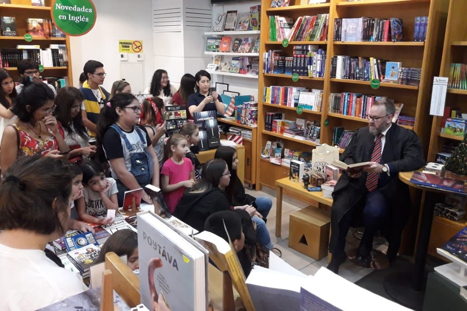Children surround a person reading a book