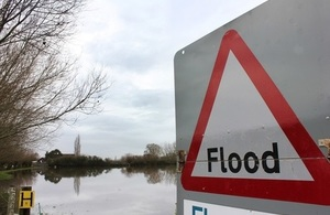 UK flood sign overlooking flooded land in rural area.