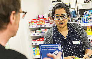 A man and a pharmacist talk over the counter