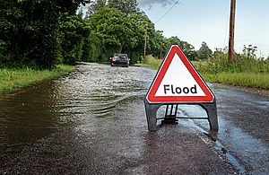 A flood sign is placed on a road. A large flood is in the background with a car driving through the flood water.