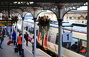 Rail station platform with passengers and hanging baskets of flowers.