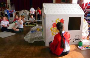 A school girl painting a Wendy House