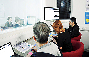 A team of colleagues working at a desk, using laptops, posters and post-it notes.