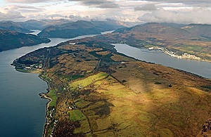 Aerial view of Her Majesty's Naval Base Clyde. You can see the green fields and the water around the edge.