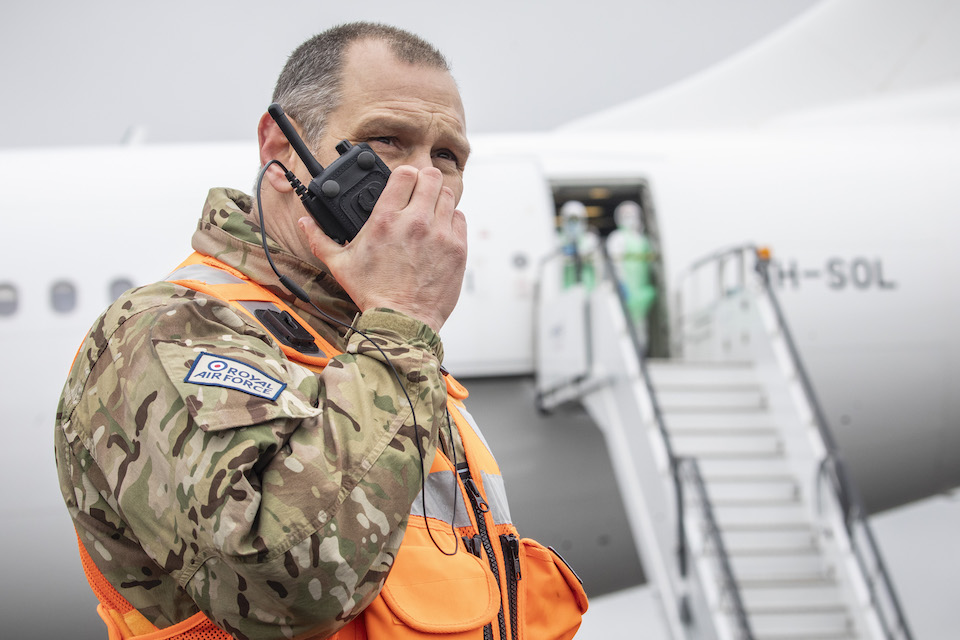 A member of Royal Air Force personnel speaks into a walkie talkie