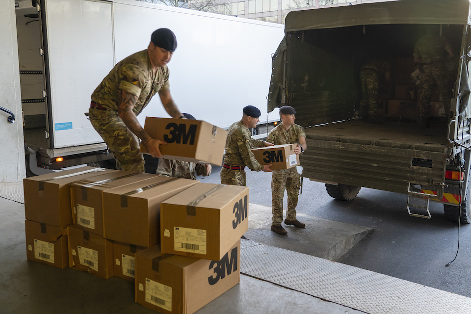 Uniformed personnel unload boxes from a lorry