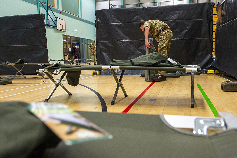 Military personnel helping to install medical equipment in a gym hall