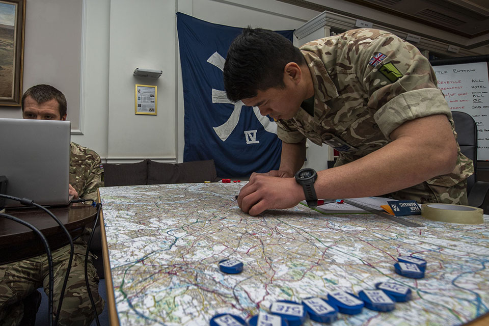 A British Army soldier moves markers across a map