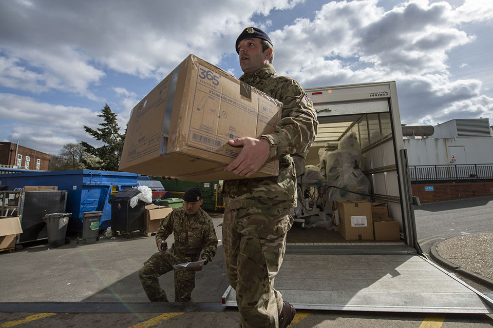 A British Army soldier carries a box from a lorry