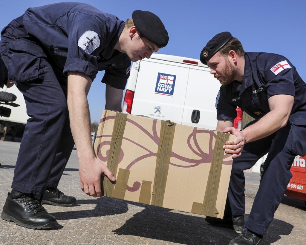 Royal Navy sailors lift a box