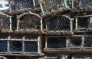 Several lobster pots used for catching lobsters are piled one on top of the other