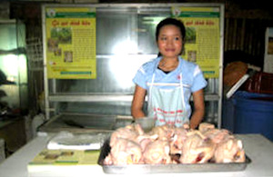 A vendor sells certified chickens in a Vietnamese market.
