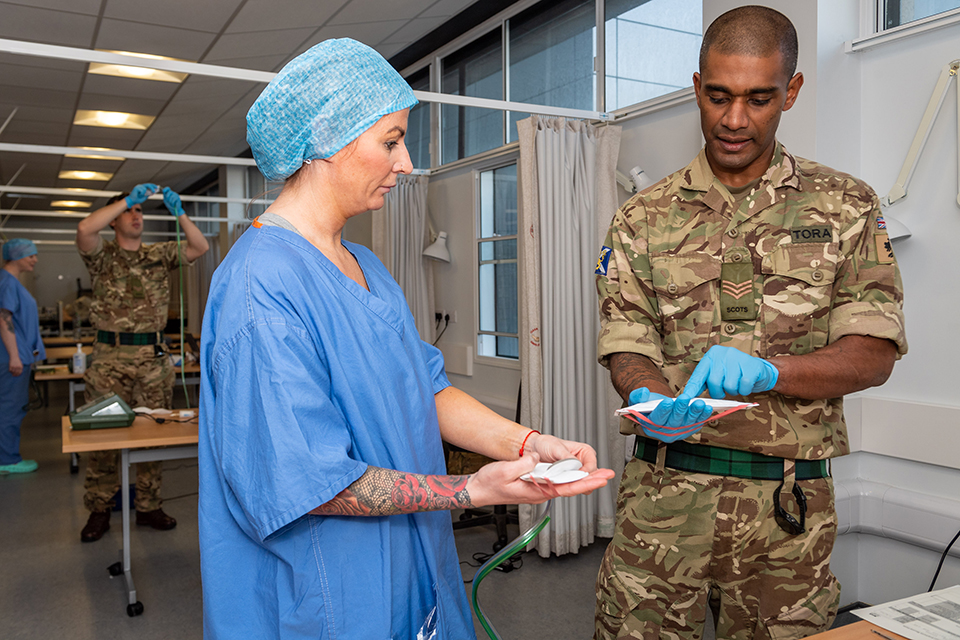 A soldier and a nurse discussing a PPE mask