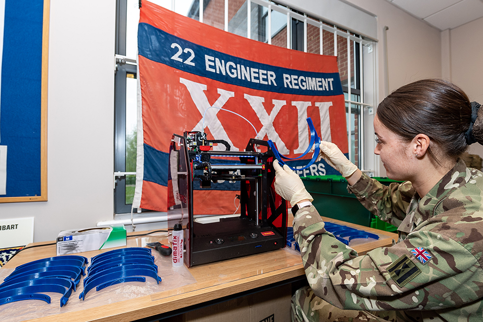 A woman in British Army uniform operates 3D printing machinery, with a row of printed objects beside her.