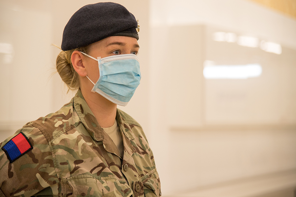A female soldier wears a PPE face mask