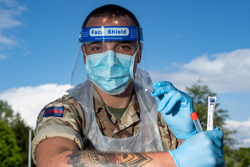 A soldier in Personal Protective Equipment holds a swab out to the viewer.