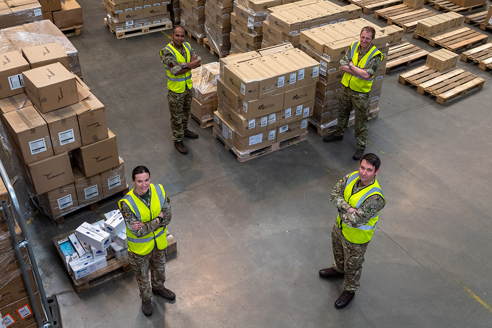 Soldiers stand surrounded by boxes of PPE.