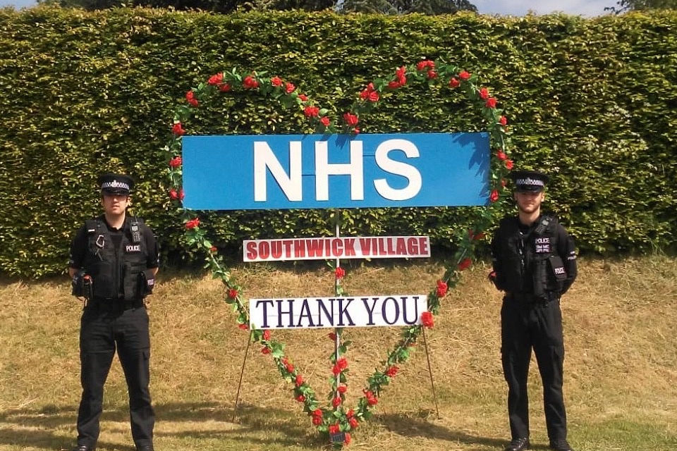 Image shows two police officers next to a handmade message of thanks to the NHS from the community at Southwick.