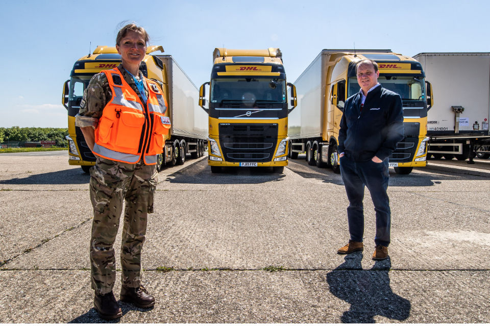 Squadron Leader Donna Rogerson standing in front of 3 HGV haulage lorries.