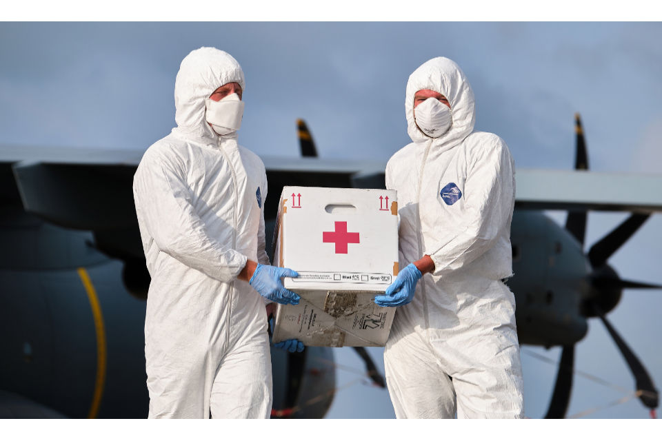 Medical supplies being carried by two individuals dressed in PPE.