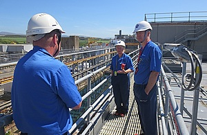 Martin Chown on the gantry of FGMSP talking to 2 other employees