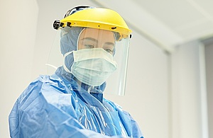 Healthcare worker wearing full PPE including face mask, visor, apron and long sleeved gown with hood