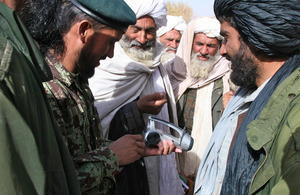 An Afghan soldier demonstrates a wind-up radio to a group of locals and elders in Helmand province (library image) [Picture: Crown copyright]