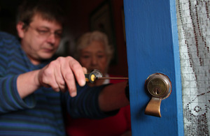 Man fitting a lock to a door