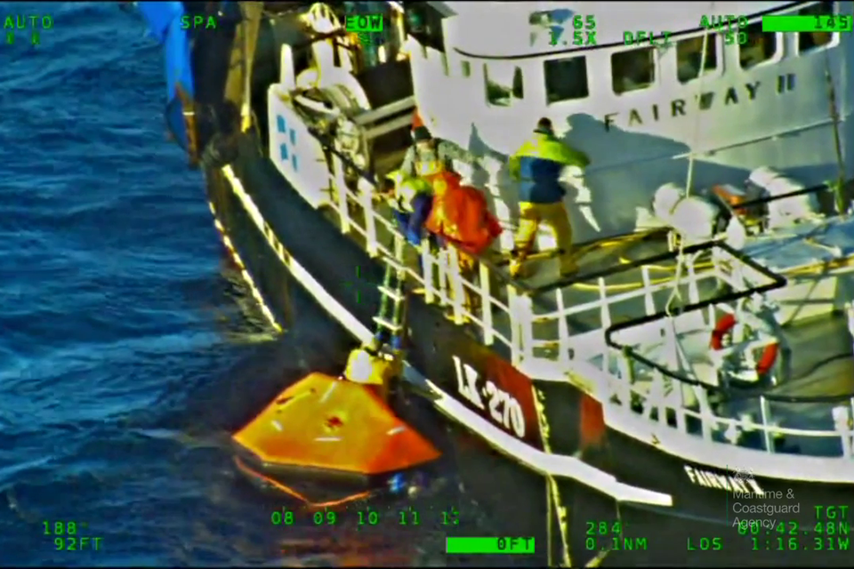 Crew being recovered from liferaft onto another fishing vessel.