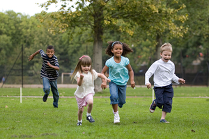 Four children running in a park