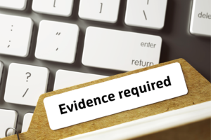 Laptop keyboard with file marked 'Evidence required' lying across it